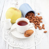 Breakfast with homemade cookies, apple and nuts with cup of tea — Stock Photo