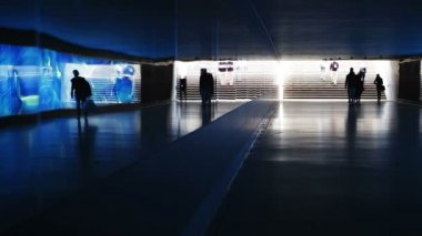 Blue illuminated underpass, subway - people walking by — Stockvideo