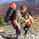 excursionista con mochila de pie en la cima de una montaña con las manos levantadas y disfrutar del amanecer — Foto de Stock   #56256545