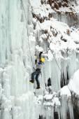Man climbing frozen waterfall — Stock Photo