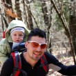 Father is hiking with the 1.5 year baby in baby carrier — Stock Photo #65426537