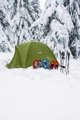 Tent winter mountains.Tent stands in the mountains in the snow. Snowshoes are beside the tent. — Stock Photo