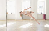 Woman practicing pole dance in a pole fitness cl — Stock Photo