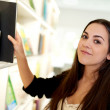 Young woman choosing the right file from the shelf — Stock Photo #73002271