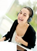 Joyful young woman laughing and listening to music — Stock Photo