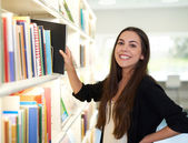Happy friendly woman choosing a book to read — Stock Photo
