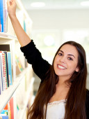 Happy friendly young woman reaching for a book — Stock fotografie