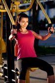 Woman exercising upper body using weights machine outside. — Stock Photo