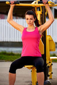 Muscular woman sitting on weights machine exercising arms. — Stock Photo