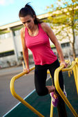 Woman looking down doing tricep dips outside — Stock Photo