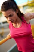 Close up of woman concentrating while doing tricep dips. — Stock Photo