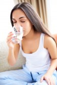 Woman drinking glass of water  leaning forward. — Stock Photo