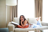 Woman lying on couch resting chin in hand. — Stock Photo