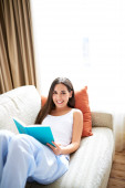Woman reclining against orange cushion looking up smiling. — Stock Photo