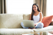 Woman sitting on couch with laptop. — Stock Photo