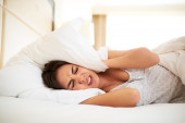 Woman lying in bed covering ears with pillow — Stock Photo