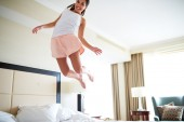 Angled view of woman jumping on bed. — Stock Photo