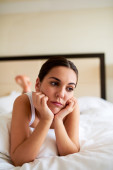 Woman lying in bed looking downcast. — Stock Photo