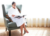 Woman sitting in chair reading book. — Stock Photo