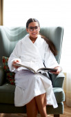 Woman sitting in chair smiling with book in lap. — Stock Photo