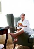Woman lounging in chair with legs over chair arm. — Stock Photo
