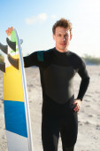 Handsome young surfer posing with his surfboard — Stock Photo