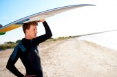 Attractive surfer balancing his board on his head — Stock Photo