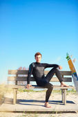 Relaxed surfer waiting on a wooden bench — Stock Photo
