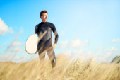 Surfer standing on a dune looking at the ocean — Stock Photo