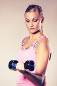 Woman looking down at weight doing bicep curl. — Stock Photo
