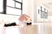 Baletka v protahovací cvičení na podlaze — Stock fotografie