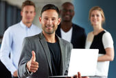 Young white executive making thumbs up sign holding laptop — Stock Photo