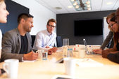 White male executive smiling at camera in work meeting — Stock Photo