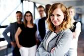 Female executive gazing at camera with arms crossed — Stock Photo