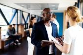 Black executive talking to white female colleague — Stock Photo