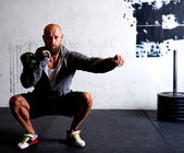 Athletic white man squatting with kettlebells — Stock Photo