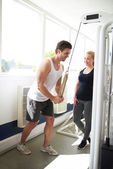 Trainer Showing how to Pull Down a Pulley to Woman — Stock Photo