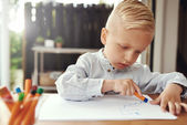 Handsome young boy drawing with crayons — Stock Photo