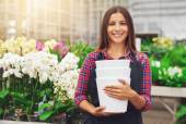 Happy young florist working in a hothouse — Stock Photo