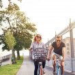 Romantic couple cycling holding hands — Stock Photo #84180534
