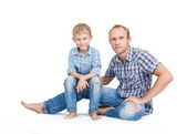 Father with son in old tattered jeans and plaid shirts on the wh — Stock Photo