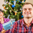 Wife gives a Christmas gift to her husband — Stock Photo #58053289