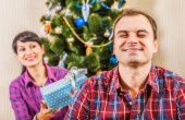 Wife gives a Christmas gift to her husband — Stock Photo