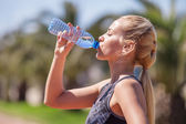 Girl drink  water after jogging — Stock Photo