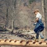 Boy walking over mountain bridge — Stock Photo #71508345