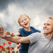 Son with father among the poppies flowers — Stock Photo #72742809