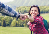 Man holds  woman helping hand — Stock Photo