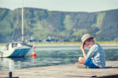 Boy sitting on wooden pier — Stock Photo