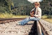 Man with guitar sitting on railway — Stock Photo