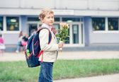 Žák chlapec s květinami — Stock fotografie